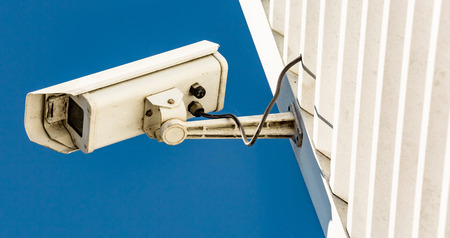 Close-up of modern CCTV camera on the wall of an industrial building