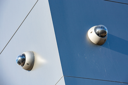 Close-up of two mini CCTV cameras on the wall of an industrial building