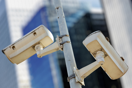 Close-up of two CCTV cameras with business buildings in the background