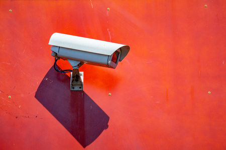 Security CCTV camera installed on a red wall in the city