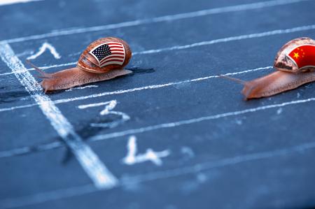 Dos caracoles con banderas en sus conchas que ilustran la guerra económica entre Estados Unidos y China Foto de archivo