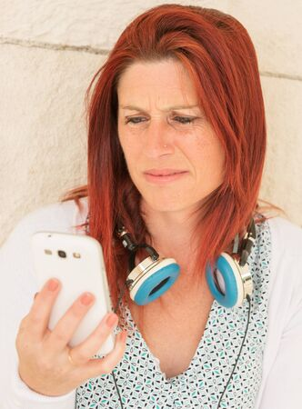 Expressive portrait of a cute red-haired woman reading the information with annoyance on her mobile phone