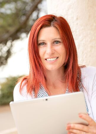 Expressive portrait of a beautiful smiling red-haired woman reading information on its touch pad