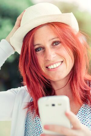 Portrait of smiling beautiful young woman close up with mobile phone, against background of summer green park.