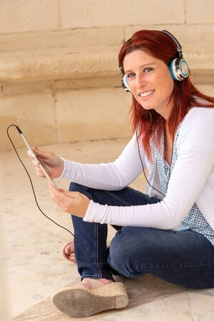 Pretty smiling redhead woman sitting on the floor listening to music or watching a movie on a touch pad