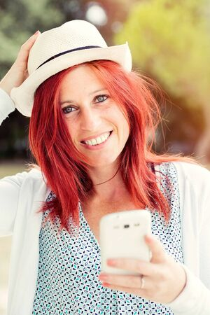 Portrait of smiling beautiful young woman close up with mobile phone, against background of summer green park. Imagens