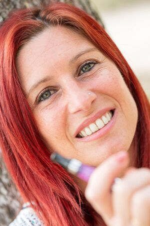 Portrait of a pretty redhead woman leaning against a tree smoking a electronic cigarette in a park