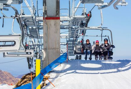La Mongie, France - March 22, 2019:Front view of three skiers riding on chairlift arrival over snowy mountain slope while resting on resort on sunny winter day