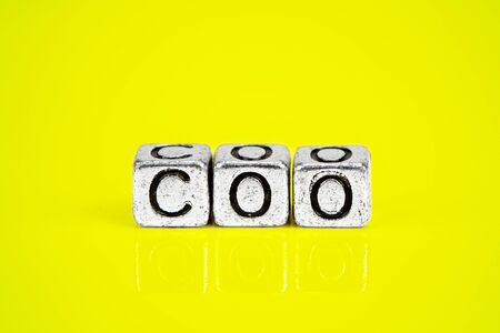 Chief Operating Officer COO concept with cubic metal letters on yellow background