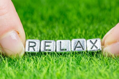 Close up on word RELAX written in metal letters laid on grass and held between the fingers of a woman. Concept of wellness background