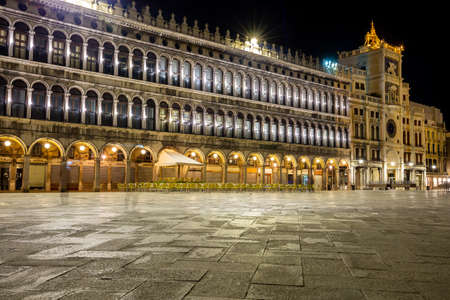 Night view of the Piazza San Marco showing a multitude of empty chairs belonging to a renowned bar. There are no more tourists on the square that has become deserted