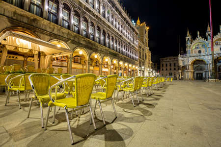 Venice, Italy - March 19, 2015:Night view of the Piazza San Marco showing a multitude of empty chairs belonging to a renowned bar. There are no more tourists on the square that has become deserted Editorial