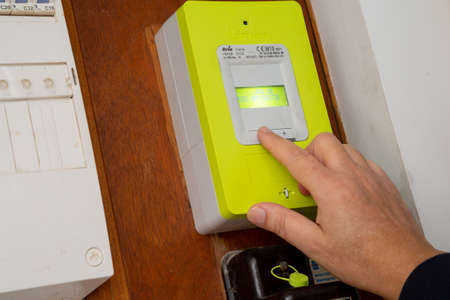 Benon - France - 21 February 2020 - Closeup of hand of man on new smart electric meter Linky from ERDF (Electricity Network Distribution France) in the entry of building