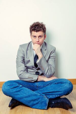 Portrait of a worried or concerned man or freelancer worker sitting legs crossed at home Stock Photo