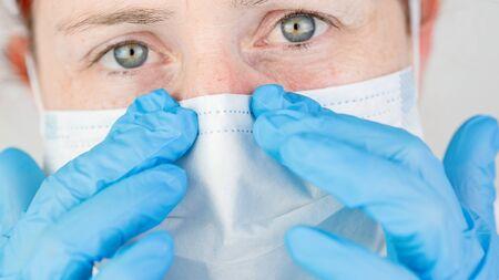 Close-up portrait of a nurse adjusting her protective surgical mask Foto de archivo