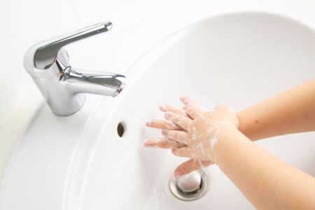 Kid cleaning and washing hands with soap in the bathroom