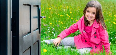 Opened door concept with a pretty young child lying in the grass in park