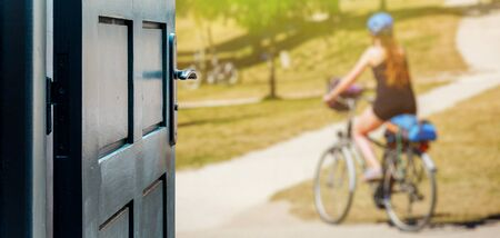 Opened door concept with a woman biking in nature on a blurred background