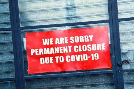 """Close-up on a red closed sign in the window of a shop displaying the message """"Permanent closure due to covid-19"""""""