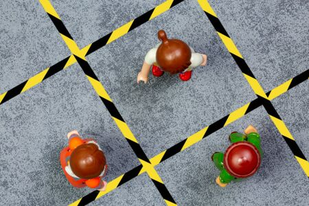 Playmobil character illustrating the marking on the ground and signage, for physical distance in the street or in the context of work to avoid transmission of the covid-19 virus