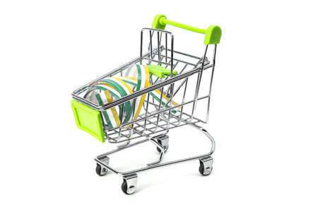 closeup on supermarket shopping cart isolated with a Irish tricolor ribbon, symbol of purchase of products made in Ireland