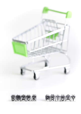 Closeup on Black Friday written with metal cubes with a supermarket trolley in the background Фото со стока