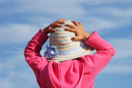 Pink-dressed toddler is trying to catch her little straw hat in windy environment. photo