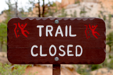 trail sign: Brown sign warning about the danger of a closed footpath in a national park. Stock Photo