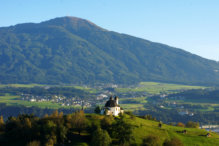 Beautiful view over this little church in front of an impressive european landscape. photo