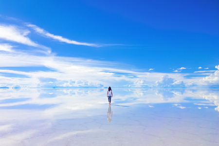 Female walks into the horizon at Salar de Uyuni, the Salt Flats in Bolivia Stok Fotoğraf
