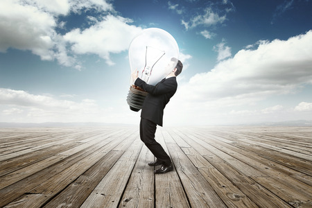 business man holding a huge bulb lamp Archivio Fotografico