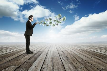 businessman Blolw away money Stock Photo
