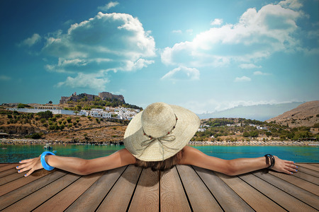 girl with straw hat rear view in lindos island Archivio Fotografico