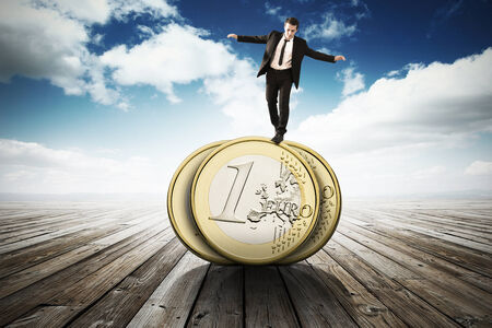business man in equilibrium on the euro coin