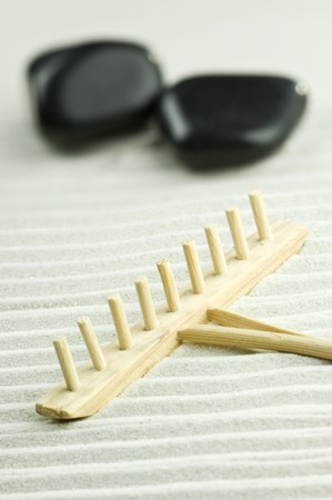 Miniature of a Zen garden with two stones and wooden rake