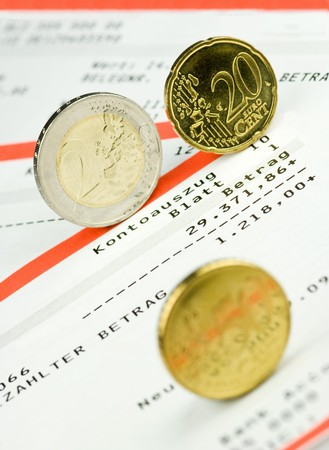 bank statement: Euro coins rolling over a bank statement