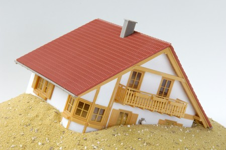 risky situation: A model house, built on sand Stock Photo