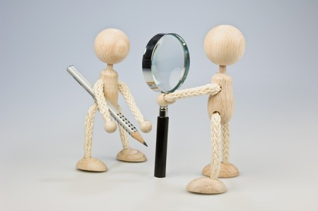 probation: Two wooden dolls looking to each other trough a magnifier