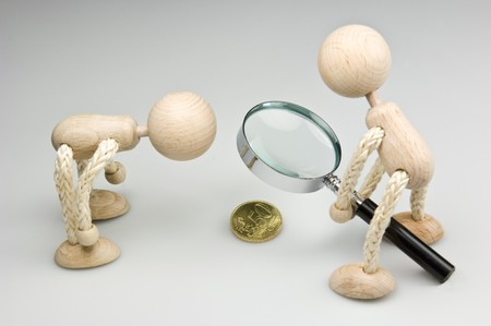 wage: Two wooden dolls looking to a Euro-Cent-Coin trough a magnifier