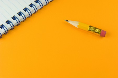 quoted: Short pencil and notepad on yellow ground Stock Photo