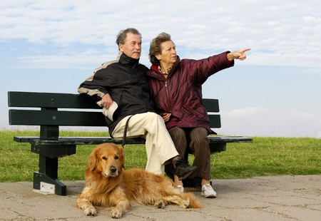 Senior couple with its dog on a park bench photo