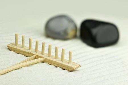 Miniature zen garden with two stones and wooden rake