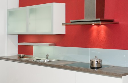 kitchenette: Modern built-in-kitchen with red wall Stock Photo