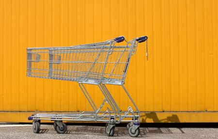 abstention: Two empty shopping carts in front of a yellow wall