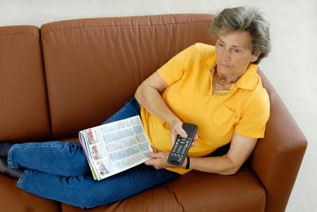 brown leather sofa: Senior woman watching TV Stock Photo