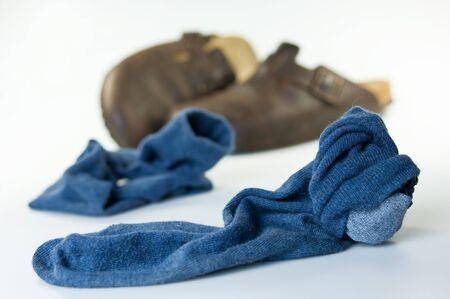 Blaue, getragene Socken und Hausschuhe liegen auf dem Boden