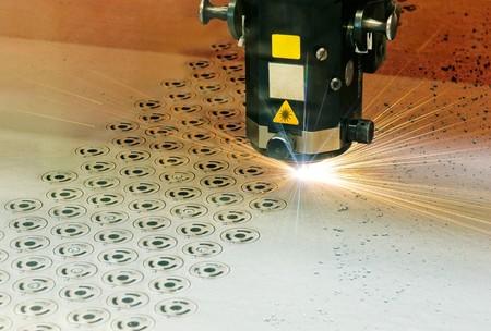 laser focus: Laserschneideger�t beim Formenschneiden aus einer Stahlblechplatte Laser cutter at work Stock Photo