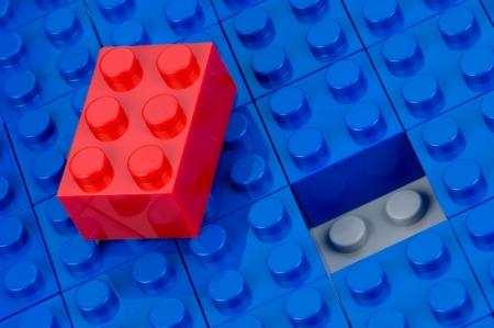 ein: Ein roter unpassender Bauklotz auf blauen liegend