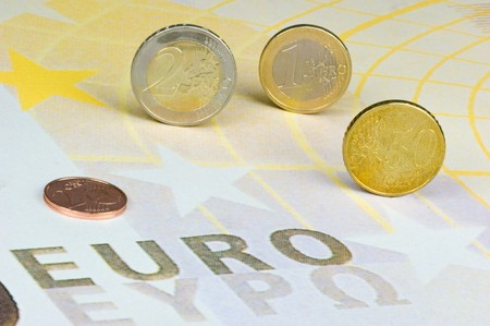 finanzen: Euromünzen rollen über einen überdimensionalen 200-Euro-Geldschein