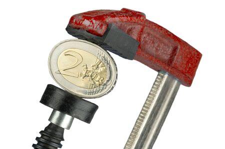 finanzen: Zwei-Euro-M�nze in einer Schraubzwinge A Two-Euro-coin in a clamp